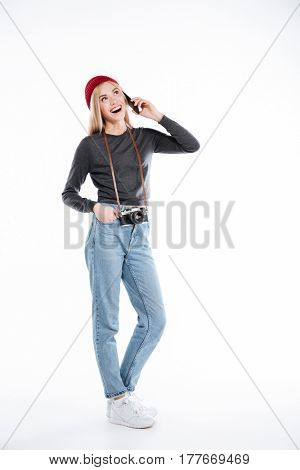 Full length of a happy smiling young woman photographer talking on mobile phone isolated over white background
