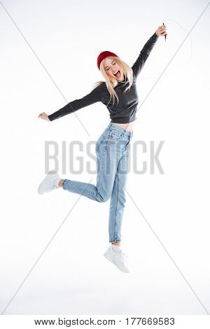 Full length portrait of a cheerful casual young woman listening music with earphones and jumping over white background