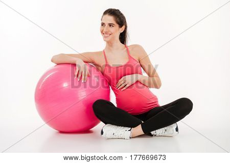 Portrait of beautiful young pregnant woman sitting with fitball and looking away isolated on white background