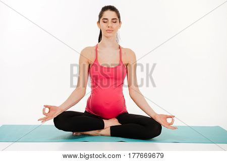 Portrait of a young pregnant woman sitting in lotus position on the mat with her eyes closed isolated on white background