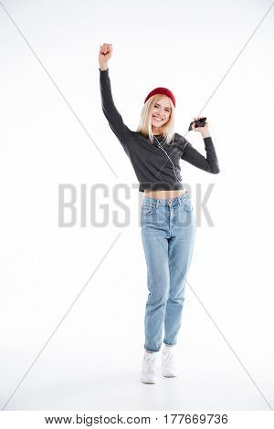 Full length portrait of a smiling happy girl listening music in earphones and dancing over white background