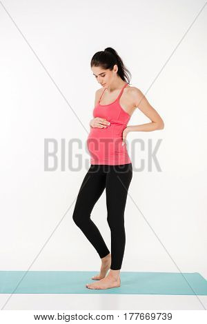 Full length portrait of a beautiful young pregnant woman in sporty outfit standing on fitness mat and smiling isolated on white background