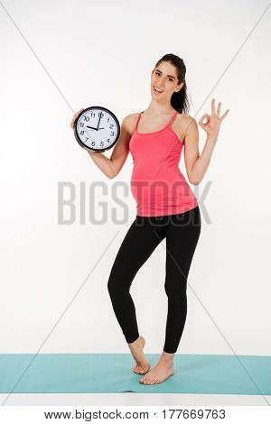 Full length portrait of a happy young pregnant woman holding an alarm clock and showing okay gesture isolated on white background