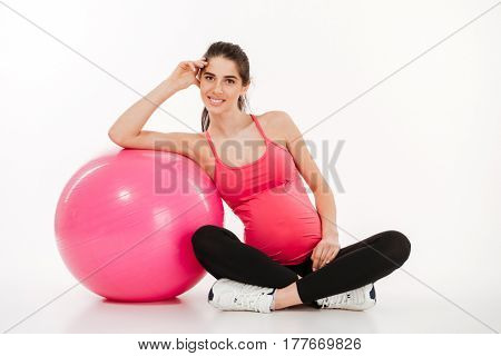 Portrait of happy smiling pregnant woman sitting with fitball and looking at camera