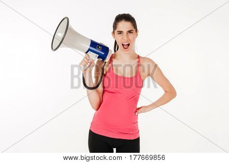 Young pregnant woman shouting in megaphone and looking at camera isolated on white background