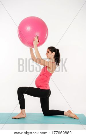 Full length portrait of a young pregnant woman doing exercises with fitball on the blue mat isolated on a white background