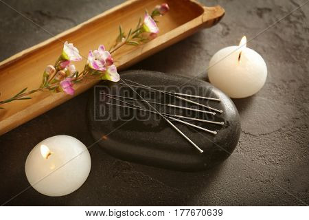 Acupuncture needles with stone and candles on textured background