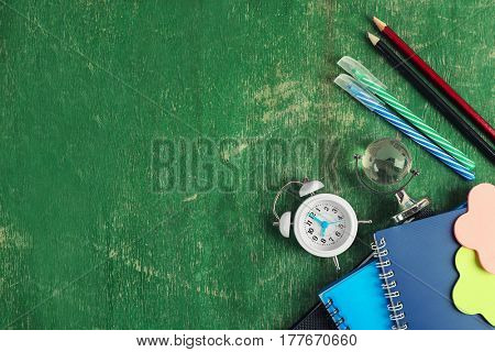 Alarm clock and stationery on wooden background