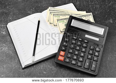 Calculator, notebook and money on grey background
