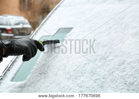 Male hand cleaning snowy car window