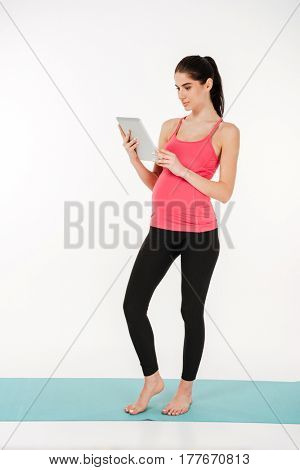 Full length portrait of a young pregant woman using tablet computer while standing on fitness mat isolated on white background
