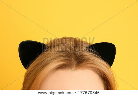 Young woman in cat ears on color background, closeup