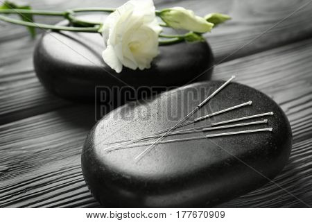 Acupuncture needles with stones on wooden background