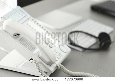 Telephone at workplace of technical support agent in office