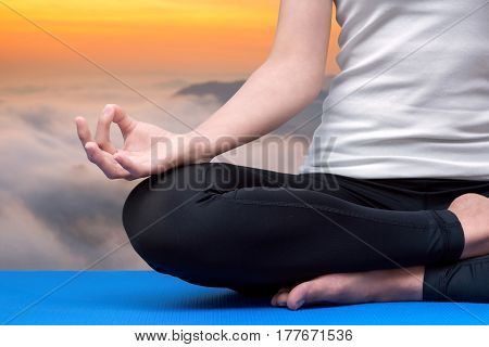 Young woman keep calm and meditates while practicing yoga to explore the Inner Peace. Yoga and meditation have good benefits for health. Photo concept for Yoga Sport and Healthy lifestyle.