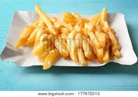 Tasty cheese fries on blue wooden table