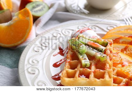 Tasty waffles with delicious fruits, ice-cream and syrup on white plate, close up