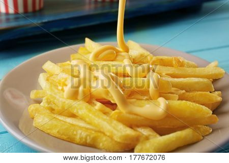 Pouring cheese sauce onto delicious fries, closeup