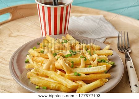 Plate with cheese fries and cup of soda water on tray
