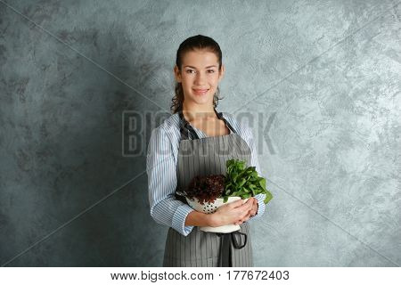 Woman in apron holding colander with fresh herbs on grey background