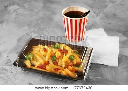 Plastic box with cheese fries and cup of soda water on table