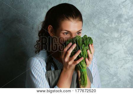 Woman in apron smelling fresh herbs, closeup