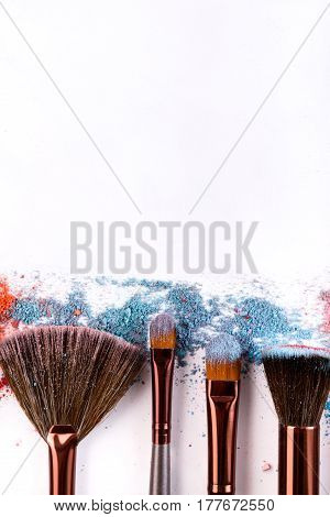 Make up and female cosmetics background. Makeup brushes vertical border with blush and eyeshadow of pink, blue and coral tones sprinkled on white.