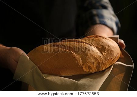 Male hands with loaf of bread on dark background, closeup
