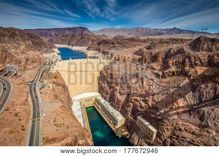 Aerial wide angle view of famous Hoover Dam a major tourist attraction located on the border between the states of Nevada and Arizona on a beautiful sunny day with blue sky and clouds in summer USA