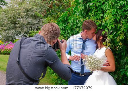 Picture Of A Man Photographer Making A Photo Of A Bride And Groom Against Green Background.