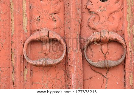 Detail of two Old handles on a red door
