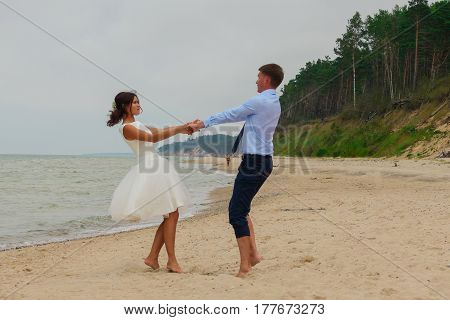 Bride And Groom Having Fun Together On The Beach.