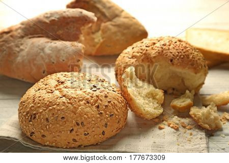 Broken buns with sesame seeds on napkin