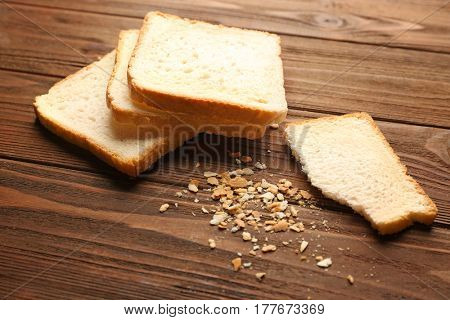 Slices and crumbs of wheaten bread on wooden background