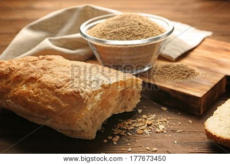 Glass bowl of bread crumbs and broken loaf on wooden table