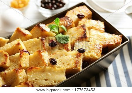 Delicious bread pudding with currant in baking dish on kitchen table