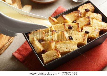 Tasty cream pouring on bread pudding with currant in baking dish