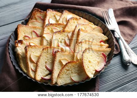 Tasty bread pudding with apples in baking dish on kitchen table