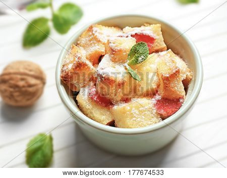 Delicious bread pudding with strawberry and mint in bowl on wooden table