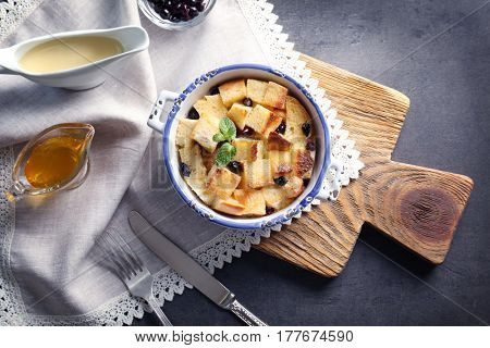 Delicious bread pudding with currant in bowl on table
