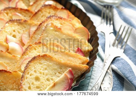 Tasty bread pudding with apples in baking dish on napkin