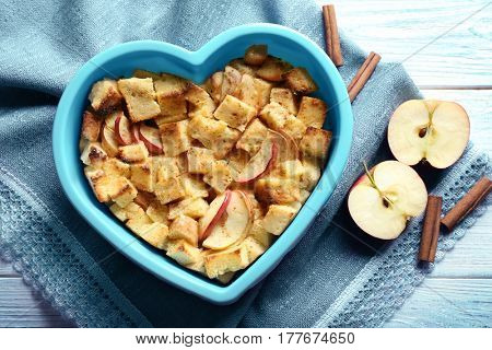 Delicious bread pudding with apples in heart shape bowl on napkin