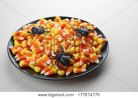 Plate with tasty Halloween candies on color background