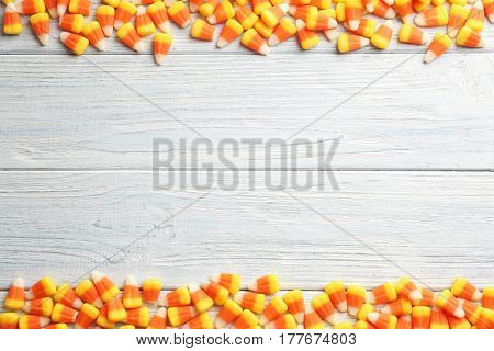 Colorful Halloween candy corns on wooden background