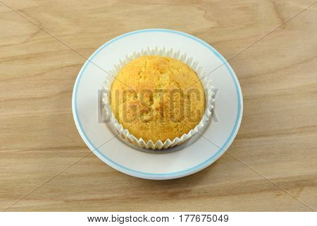 One cornbread muffin in paper muffin cup on small bread plate