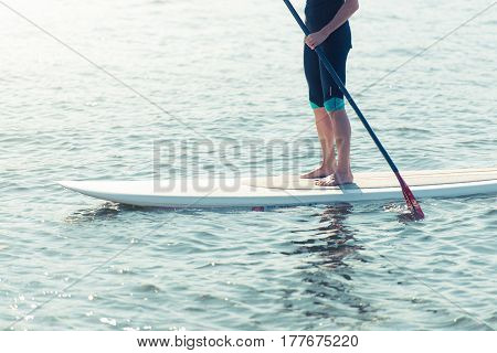Man standing on the paddleboard in water