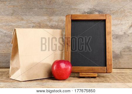 Paper lunch bag, red apple and small blackboard on wooden background