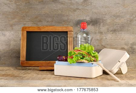 Delicious food in lunch box on wooden background