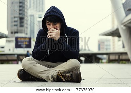 Lonely man sitting on the ground in urban scene