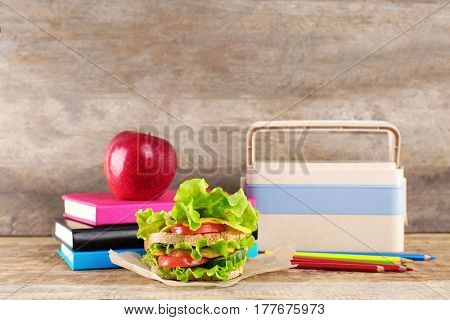 Delicious food, lunch box and school accessories on wooden background